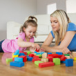 Mother and daughter playing with building blocks on floor — Stock Photo #51593911