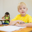 Постер, плакат: Pupils colouring at desks in classroom