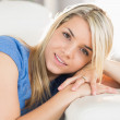 Portrait of a smiling young woman sitting on sofa — Stock Photo #51594491
