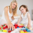 Mother and daughter playing with building blocks on bed — Stock Photo #51594755