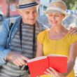 Happy tourist couple using guide book in the city — Stock Photo #51594769