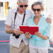 Happy tourist couple using tour guide book in the city — Stock Photo #51595583
