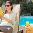 Woman reading book by pool with breakfast on table — Stock Photo #51595695