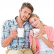 Attractive young couple sitting holding mugs — Stock Photo #51596107