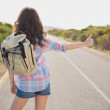 Woman hitchhiking on countryside road — Stock Photo #51596735