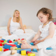 Mother and daughter playing with building blocks on bed — Stock Photo #51597133