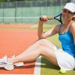 Pretty tennis player sitting on court smiling at camera — Stock Photo #51597259