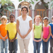 Teacher standing with pupils in courtyard — Stock Photo #51597519