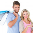 Attractive young couple holding shopping bags using tablet pc — Stock Photo #51598325
