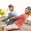 Happy mature couple riding a scooter in the city — Stock Photo #51598521