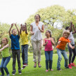 Teacher jumping with pupils outside — Stock Photo #51598875