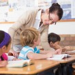 Teacher helping pupil in classroom — Stock Photo #51599245