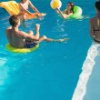 People playing with ball in swimming pool — Stock Photo #51599429