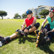 Fit mature couple tying up their roller blades on the grass — Stock Photo #51599957