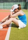 Upset tennis player sitting on court  — Foto Stock