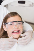Dentist putting mouth retractor on girl — Foto de Stock