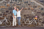 Happy senior couple going for a bike ride in the city — Zdjęcie stockowe