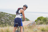 Portrait of athletic man mountain biking — Stock Photo
