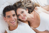 Young couple lying in bed at home — Stock Photo