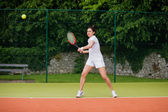 Pretty tennis player about to hit ball — Stock Photo