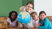 Pupils and teacher in classroom with globe — Stok fotoğraf