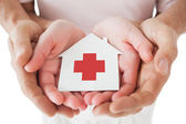 Couple holding paper house with red cross in hands — Stock Photo