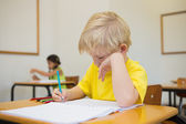 Pupils colouring at desks in classroom — Foto Stock