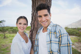 Smiling couple standing by tree trunk — Foto de Stock