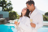 Couple with champagne flutes by swimming pool — Stock Photo