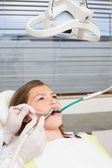 Pediatric dentist examining little girls teeth — Стоковое фото