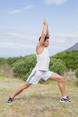 Man doing stretching exercises on countryside landscape — Stock Photo