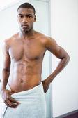 Serious shirtless muscular man in gym — Stock Photo