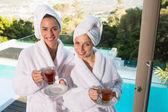 Smiling women in bathrobes having tea — Stock Photo
