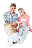 Attractive young couple sitting holding a house outline — Stock Photo