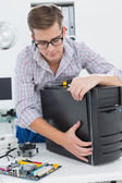 Young technician working on broken computer — Stock Photo