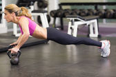 Side view of woman doing push ups with kettle bells in gym — Stock Photo