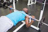 Young man lifting barbell in gym — 图库照片