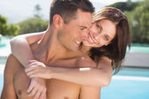 Woman embracing man by swimming pool — Stock Photo