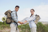 Hiking couple holding hands on mountain terrain — Stock Photo
