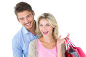 Attractive young couple holding shopping bags — Stock Photo