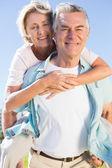 Happy senior man giving his partner a piggy back — Stock Photo