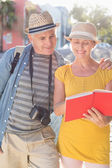 Happy tourist couple using guide book in the city  — ストック写真