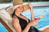 Beautiful woman holding drink by swimming pool — Stock Photo