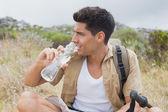 Hiking man drinking water on mountain terrain — Stock Photo
