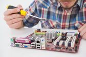 Computer engineer working on cpu with screwdriver — Stock Photo