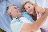Happy senior couple cuddling on blanket — Stock Photo