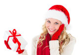 Festive blonde smiling at camera holding present — Stock Photo