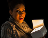 Girl opening a glowing gift — Stock Photo