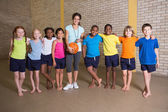 Cute pupils smiling with PE teacher — Stock Photo