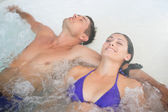 Relaxed couple in swimming pool — Stock Photo